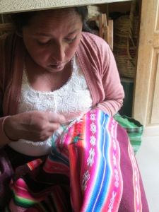 Doña Máxima Stitching the 2 Halves of the Aguayo Together